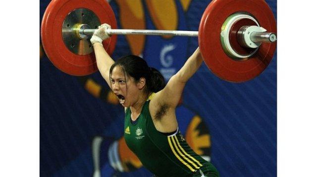 Esto es una fotografía donde se ve a la pesista Seen Lee levantando una pesa larga de gimnasia y con el vello de sus axilas al descubierto.